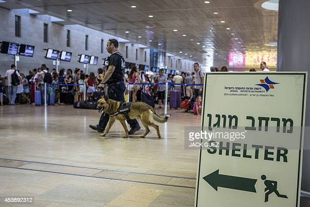 A security officer leads a dog as they patrol the hall past a sign directing passengers to a shelter of Ben Gurion International airport near the...