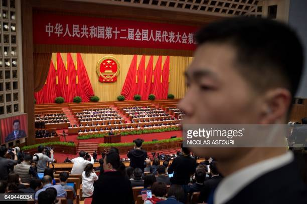 A security officer looks on during the second plenary session of the National People's Congress China's legislature at the Great Hall of the People...