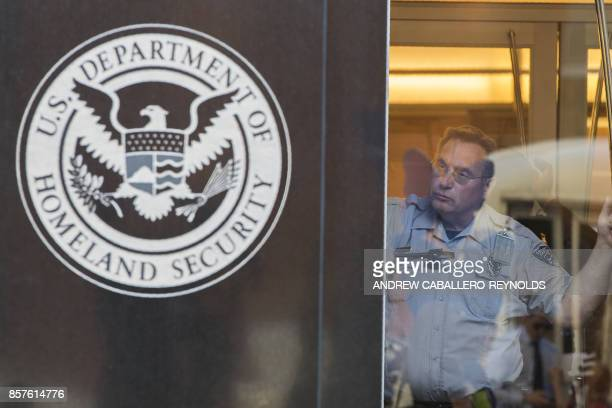 A security officer looks out of a window at the US Immigration and Customs Enforcement office part of the Department of Homeland Security in...