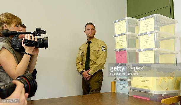 A security officer of the Higher Regional Court Munich watches cameramen take pictures of boxes filled with media accreditation demands for the NSU...