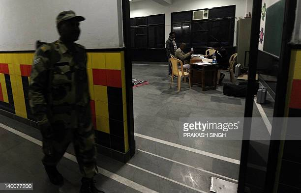 Security officer passes by as polling officers set up a polling booth at a school in Ghaziabad, Uttar Pradesh on February 27, 2012. The sixth phase...