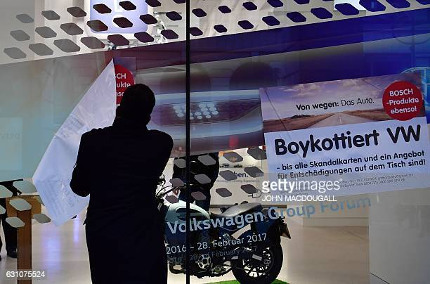 A security officer removes placards calling for a boycott of Volkswagen cars from the windows of Volkswagen's main showroom in Berlin on January 6...