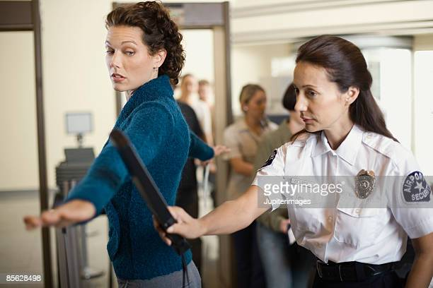 security officer searching businesswoman at airport - security check - fotografias e filmes do acervo