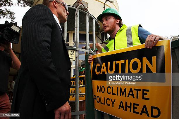 A security officer speaks with a protester as he waits for Australian Opposition Leader Tony Abbott at Penrice Soda factory on September 3 2013 in...