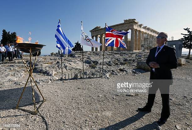 A security officer stands by a cauldron with the Olympic Flame atop the Athens Acropolis on May 16 2012 during a ceremony The Olympic flame will be...