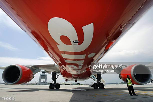 A security officer stands by AirAsia X's first leased Airbus A330 longhaul aircraft as it sits on the tarmac of the Kuala Lumpur International...