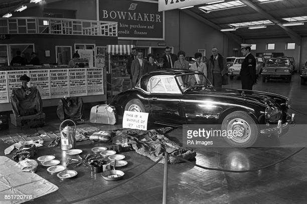 A security officer stands by as members of the public inspect a black Austin Healey car bought by Bruce Reynolds on 9 August the day after the Great...