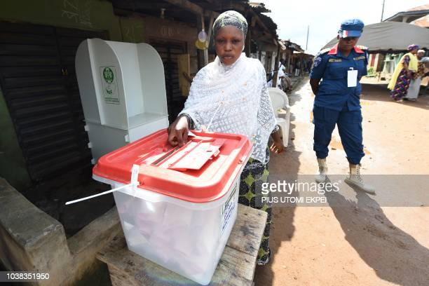 A security officer stands guard near a woman casting her vote outside in the street during the Osun State gubernatorial election in Ede in the Osun...