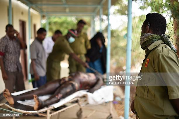 A security officer stands next to the body of one of the suspected attackers involved in the Moi University attack on April 4 2015 in the...