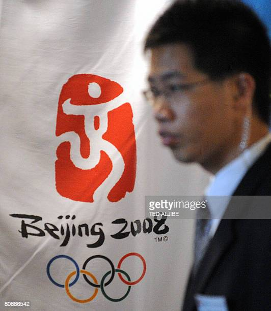 A security officer stands next to the logo of the Beijing Olympic Games during the opening of the Beijing 2008 Olympics flagship store inside the...