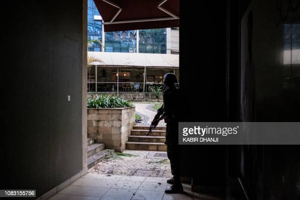 A security officer takes cover in the building attached to the DusitD2 hotel in Nairobi on January 15 after a blast followed by a gun battle rocked...