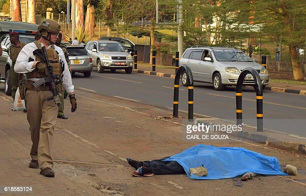 A US security officer walks past the body of an assailant after he was shot and killed by Kenyan police outside the US embassy in the capital Nairobi...