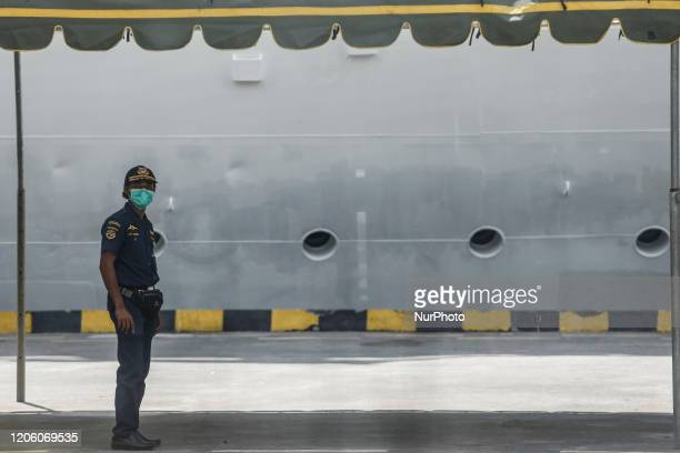 Security officer wearing face mask as cruise passengers entering the port from tourism activities at Benoa cruise port in Denpasar Bali Indonesia on...