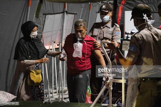 Security officers and a relative help a COVD-19 patient to a bed inside the emergency tent outside Bekasi Public Hospital Hospitals in Java,...