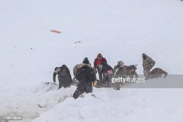 Security officers and villagers carry a victim of an avalanche near the town of Bahcesehir, in the eastern Turkey province of Van, on February 5,...