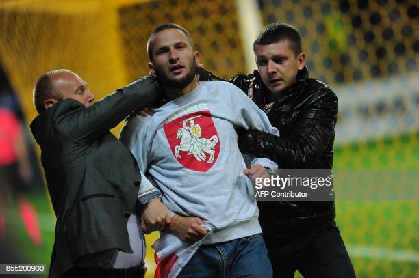 Security officers detain a pitch invader during the UEFA Europa League Group H football match between FC BATE Borisov and Arsenal FC in Borisov...