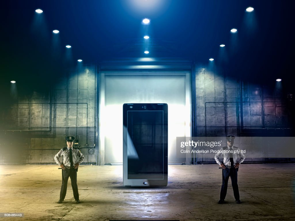 Security officers guarding tablet computer : Stock Photo