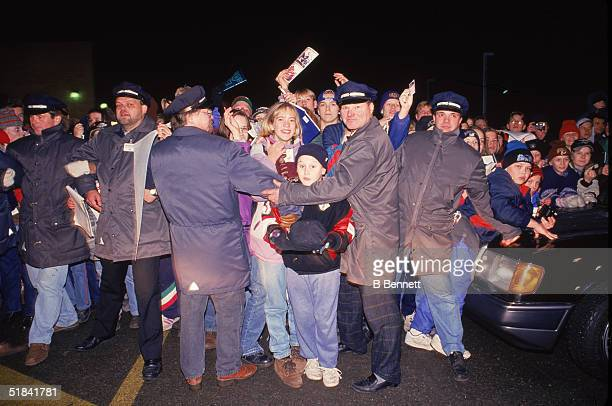 Security officers hold back a crowd of fans and supporters who want to see the players at one of the stops on the NinetyNine All Stars Tour somewhere...
