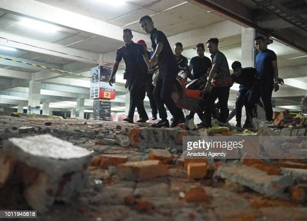 Security officers lift a motorcycle in Galeria Mall after a magnitude 70 earthquake shook eastern Indonesia on August 6 2018 at the Denpasar district...
