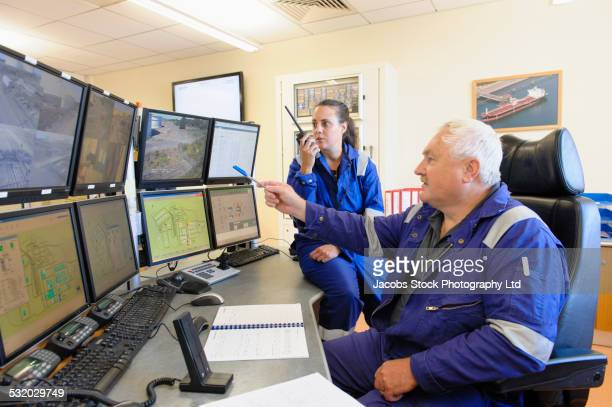 Security officers monitoring screens in control center