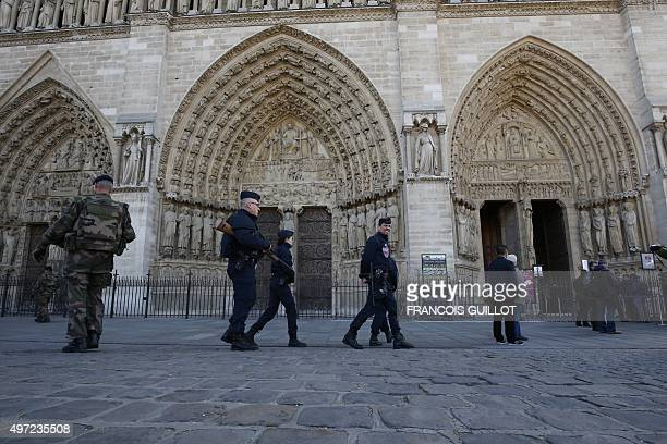 Security officers patrol next to the entrance of Notre Dame cathedral in Paris on November 15 2015 Islamic State jihadists claimed a series of...