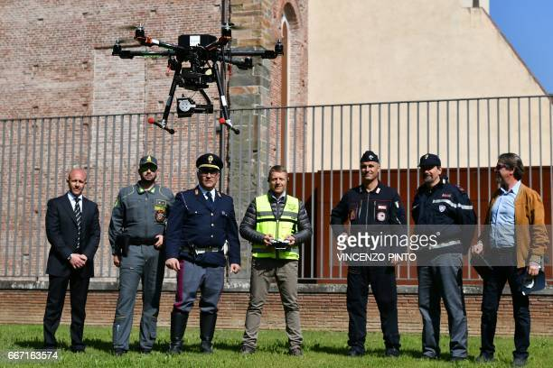 Security officers policemen and carabinieri look at a drone equipped with a thermal camera flying to securize the area during the meeting of Foreign...