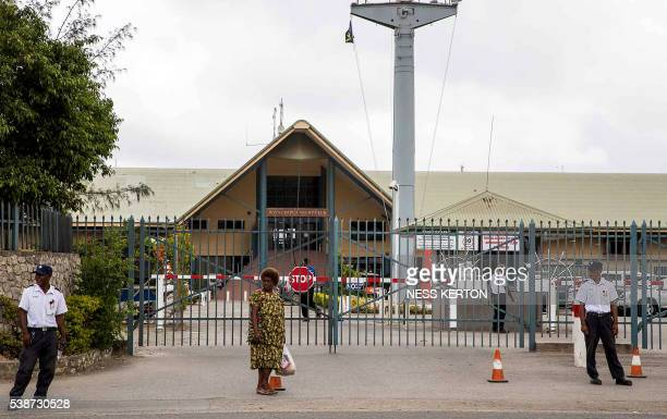 Security officers stand guard in front of the closed gate of the Royal Papua Yacht Club following a protest rally by the students in Port Moresby on...