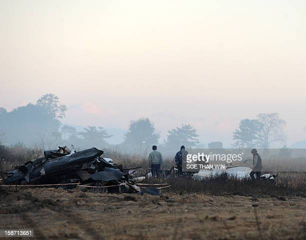Security officers stand guard near the remains of a plane that crash landed the day before near Heho airport in southern Shan state on December 26...