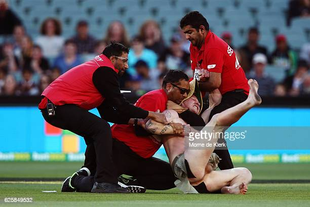 Security officers tackle a streaker during day three of the Third Test match between Australia and South Africa at Adelaide Oval on November 26 2016...