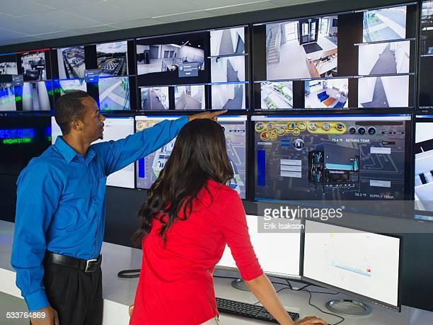 security officers watching surveillance cameras - ayudante fotografías e imágenes de stock