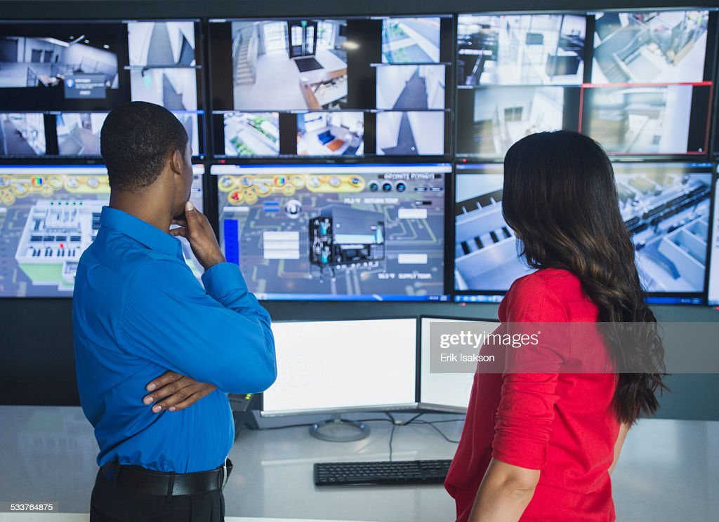 Security officers watching surveillance cameras : Foto stock