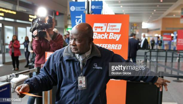 A security official gestures with one of the new orange tickets as Massport officials launch the new Logan Express services at Boston Logan...