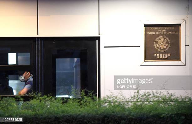 Security official keeps watch from a window in front of the US consulate in Chengdu, southwestern China's Sichuan province, on July 26, 2020. - The...