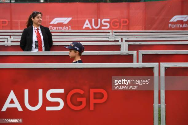 Security official looks on as a young spectator leaves after the cancellation of the Australian Grand Prix in Melbourne on March 13, 2020. - The...