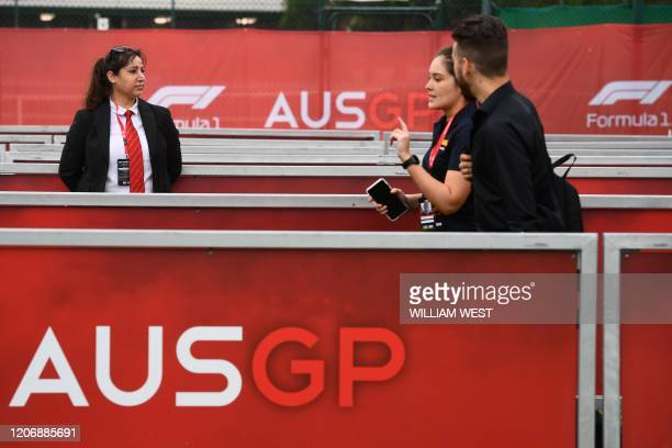 Security official looks on as spectators leave after the cancellation of the Australian Grand Prix in Melbourne on March 13, 2020. - The...