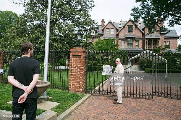 STATES MAY 9 A security official questions Colin Anhut a native of Raleigh NC after taping a sign on the gate outside of the Governor's Mansion in...