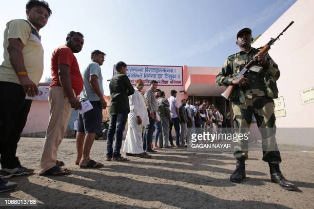Security official stands guard as voters queue outside a polling station to vote in India's Madhya Pradesh state assembly election in Bhopal on...