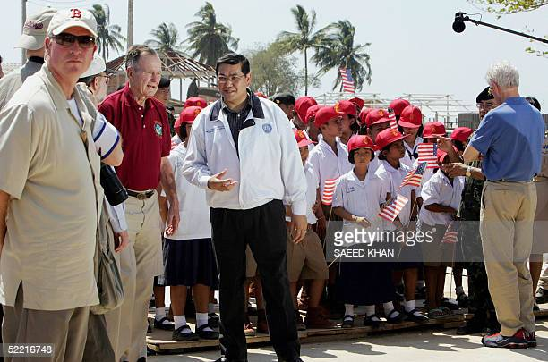 US security official stays alert as former US presidents George Bush Senior and Bill Clinton meet Thai children who lost their parents in the tsunami...