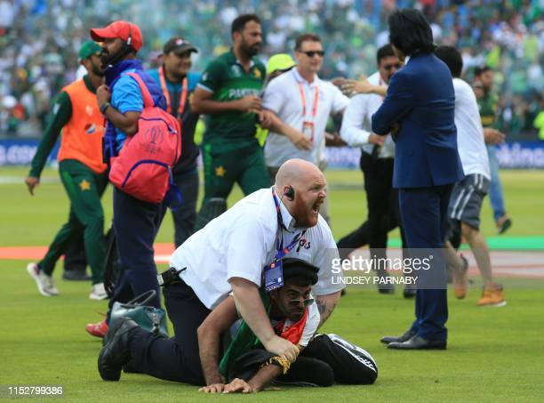 TOPSHOT A security official stops a pitch invader after the 2019 Cricket World Cup group stage match between Pakistan and Afghanistan at Headingley...