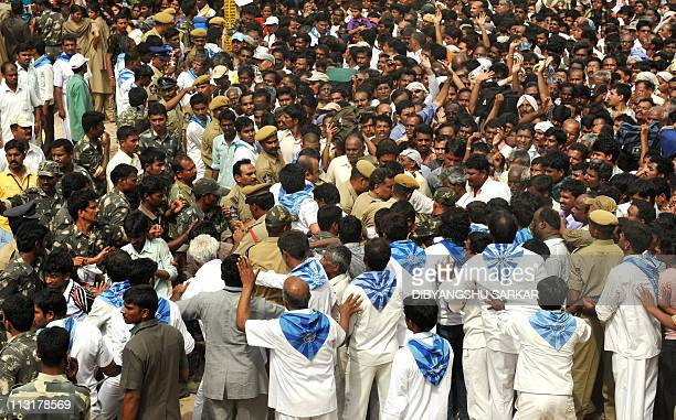 Security officials and volunteers try to controll devotees as they try to make their way to pay their last respects to Hindu guru Sathya Sai Baba...