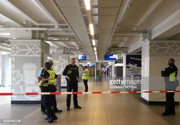 Security officials cordon off an area inside The Central Railway Station in Amsterdam on August 31 after two people were hurt in a stabbing incident