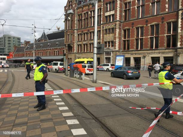 Security officials cordon off an area outside The Central Railway Station in Amsterdam on August 31 after two people were hurt in a stabbing incident