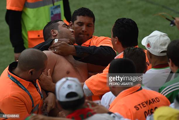 Security officials detain a matchgoer ahead of the Group H football match between South Korea and Algeria at The BeiraRio Stadium in Porto Alegre on...