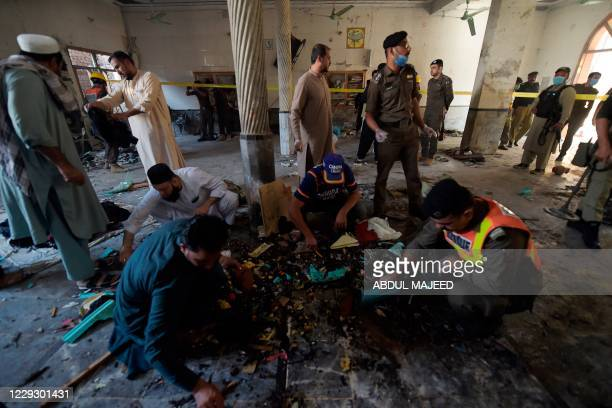 Security officials examine the site of a blast at a religious school in Peshawar on October 27, 2020. - At least four students were killed and dozens...