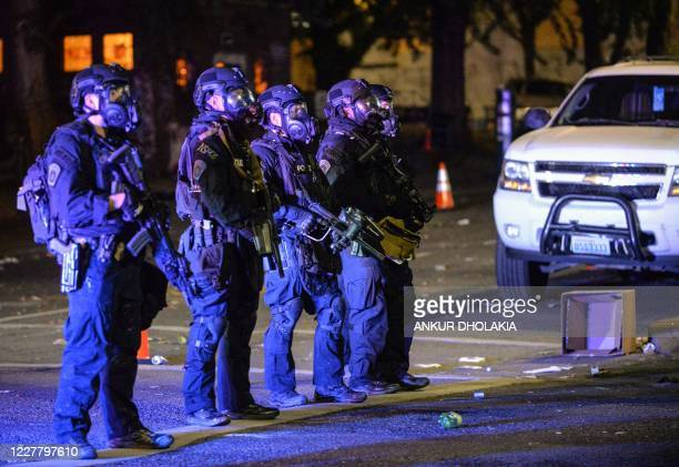 Security officials form a line across a street in Portland, Oregon early July 26 as protests continue across the United States following the death in...
