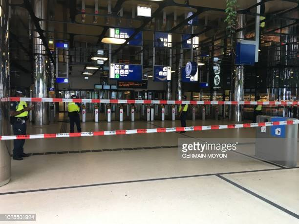 Security officials stand alert at The Central Railway Station in Amsterdam on August 31 after two people were hurt in a stabbing incident