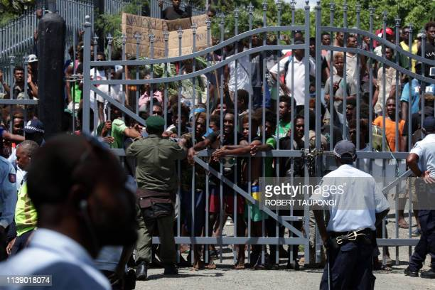 TOPSHOT Security officials stand guard as protestors gather outside the Parliamnet House during the veteran politician Manasseh Sogavare press...