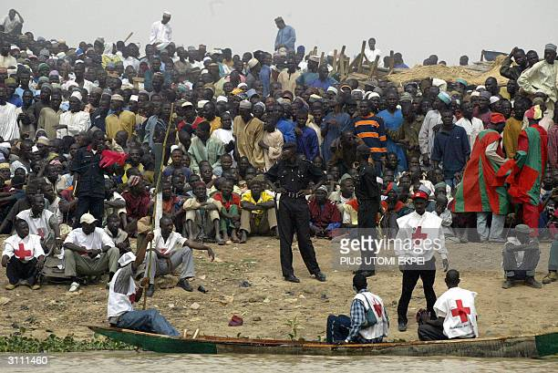 Security operatives and Red Cross officials keep watch at the crowd and fishermen catches fish at the Argungu fishing festival Friday 18 March 2004...