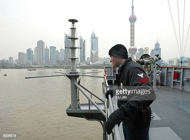 Security patrolman Drew Koehler checks the situation onboard the USS Blue Ridge as the new financial zone Pudong district is seen in the background...