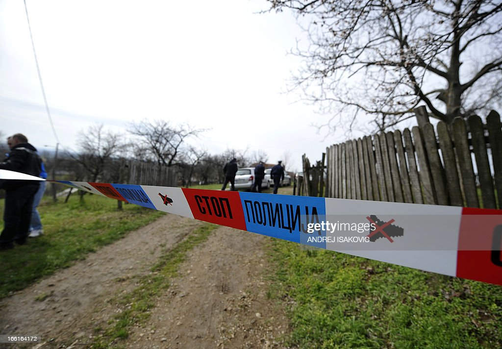 A security perimeter has been set at the entrance of a yard in the village of Velika Ivanca, 40 kilometres south of capital Belgrade, on April 9, 2013, where a man shot dead 13 relatives and neighbours, including a two-year-old child, in the country's worst killing spree in two decades..